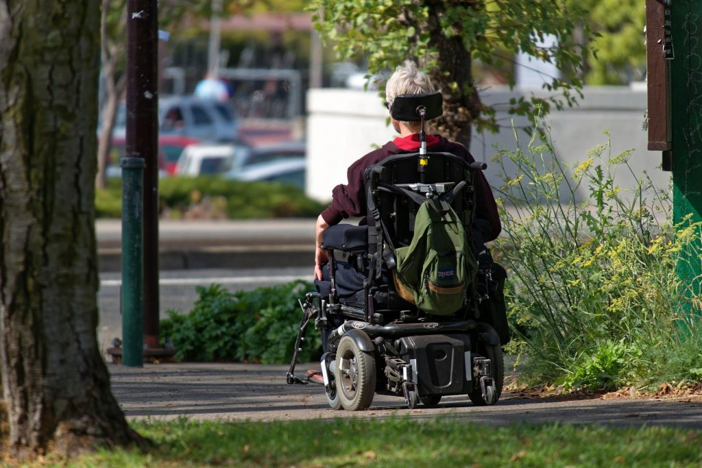 This image shows a person using a motorized wheelchair on a sidewalk.