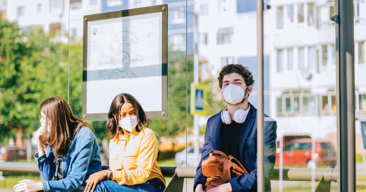 This image shows three people wearing masks while seated at an outdoors bus station during the day. Behind them is a map displaying the bus route.
