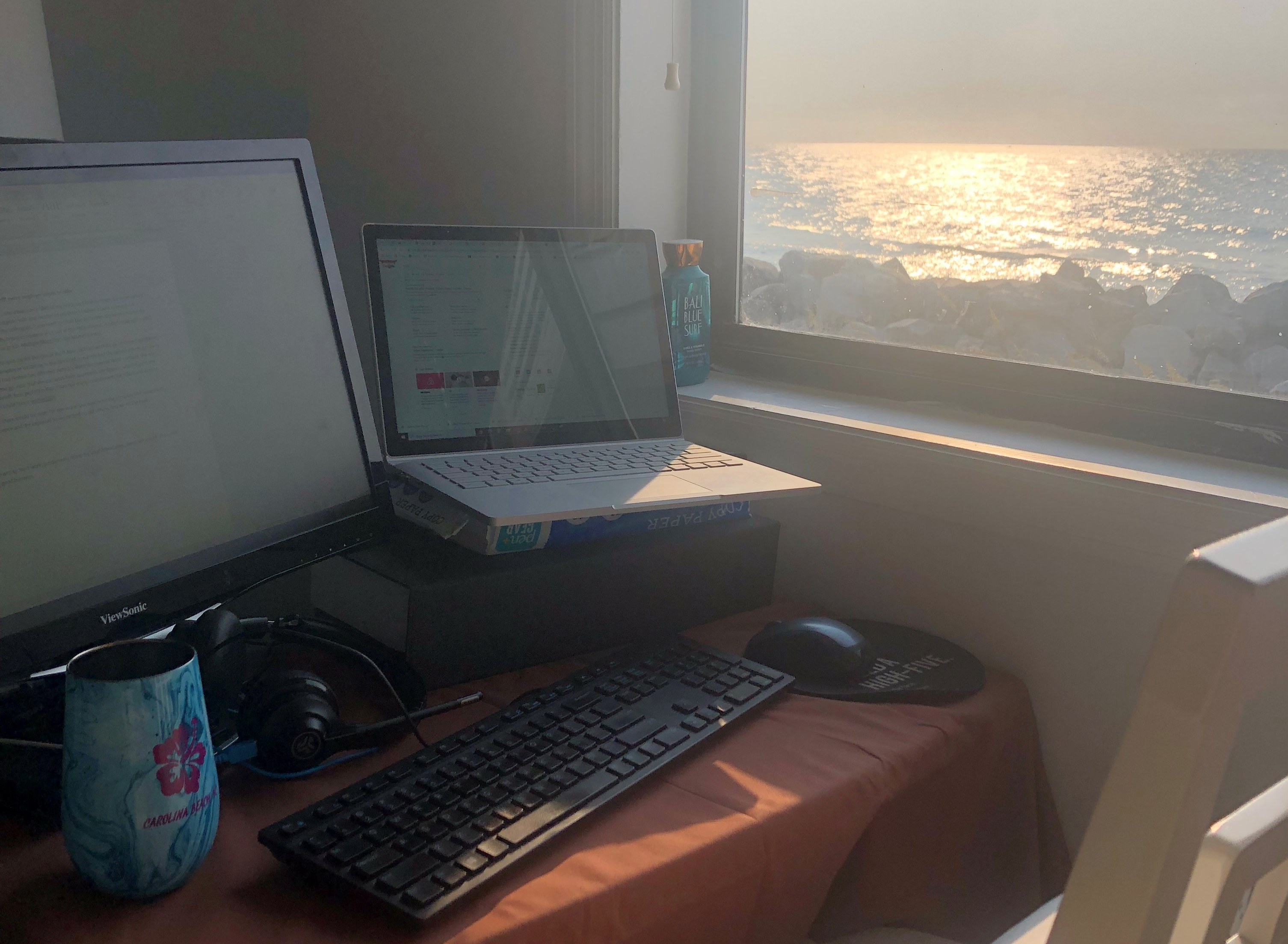 This image shows a computer on a desk with a window that has a view of the ocean.